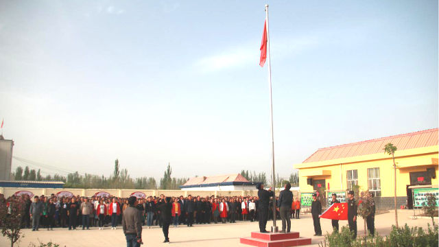 The people in a locality in Xinjiang are organized to hold a flag raising ceremony(Online image)