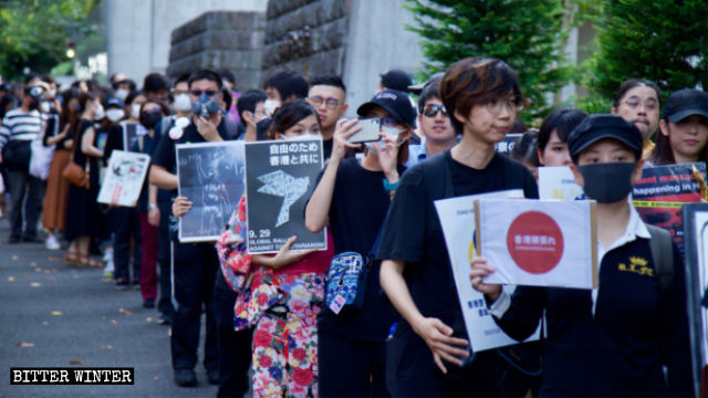A woman in kimono walks in the anti-totalitarianism march in Tokyo.